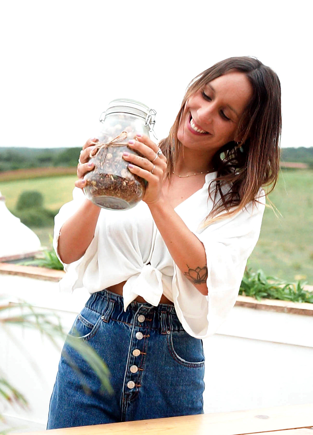 picture of Aida holding a jar with the prepared granola