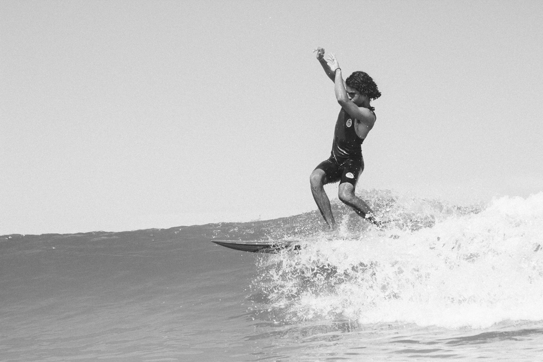 Black and white photo of a surfer surfing a wave