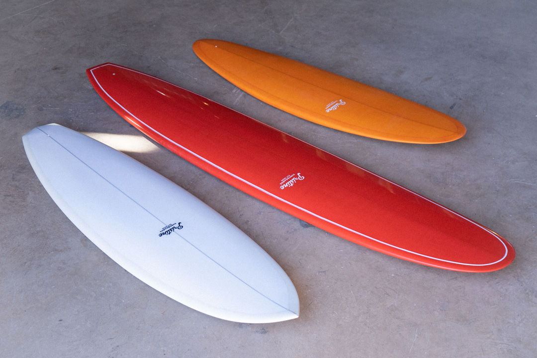 three different Pristine surfboard models laying next to each other on the floor