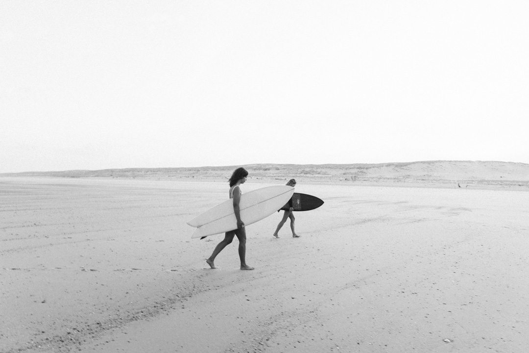 black and white photo of 2 women at the beach, carrying their surfboards