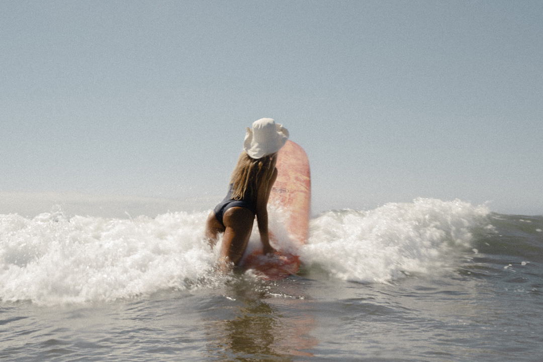 photo of the back of a female surfer trying to get into the lineup