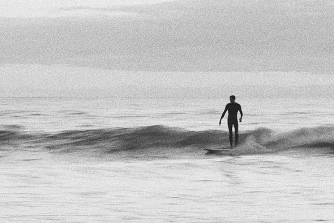 black and white silhouette of a man surfing