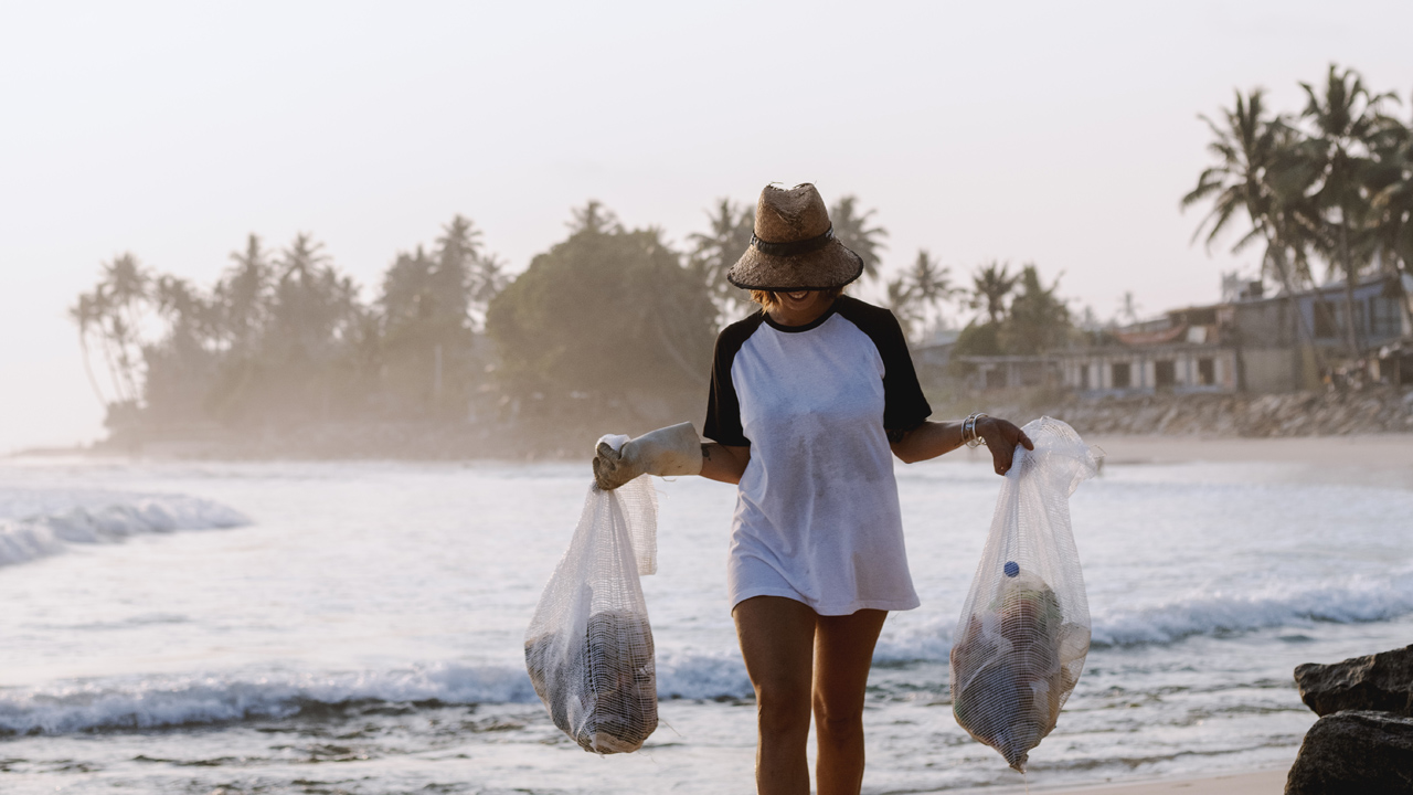 Girl collecting trash on a beach in Bali.