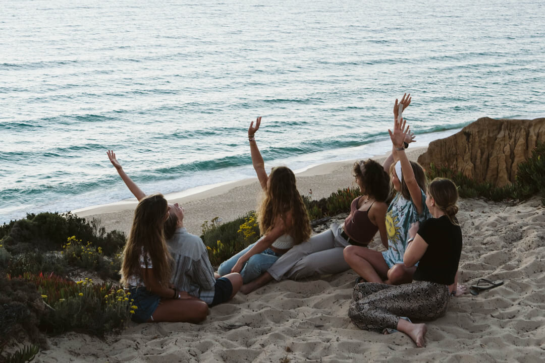 A group of girls sitting on the edge of a cliff, cheering towards the ocean.