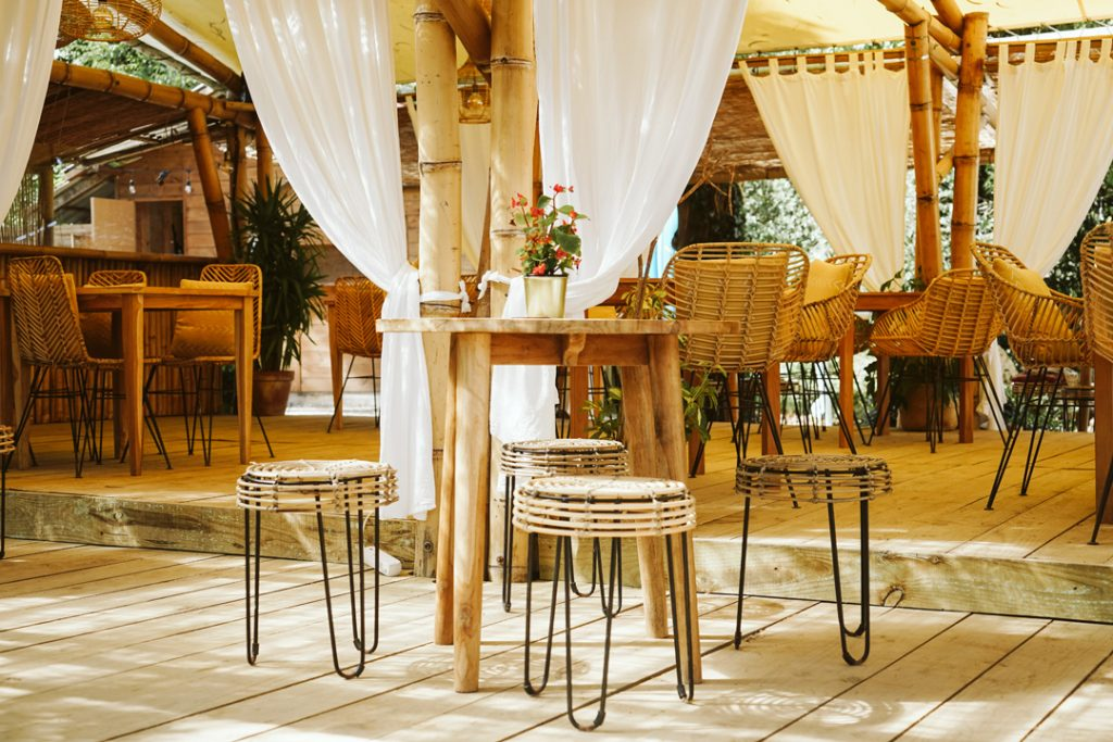 Table set-up with four stools standing outside in front of the dining area of Dreamsea Cantabria, Spain