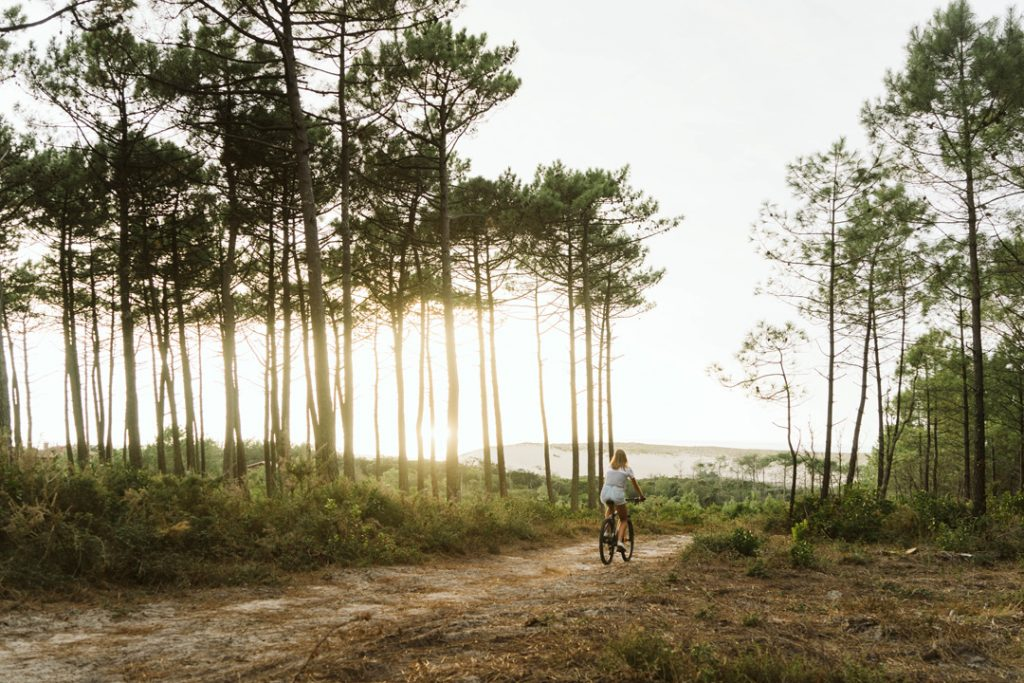 A girl riding a mountainbike through the local forest of Moliets-et-Maa, France.